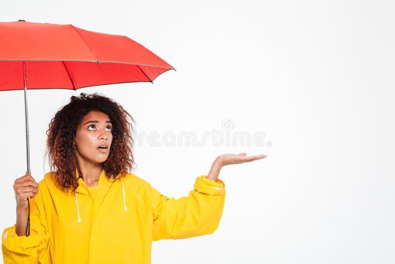 Beeld van verwarde Afrikaanse vrouw in regenjas het verbergen onder paraplu royalty-vrije stock foto