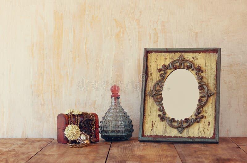 Beeld van victorian uitstekende antieke klassieke kader, juwelen en parfumflessen op houten lijst Gefiltreerd beeld royalty-vrije stock afbeelding