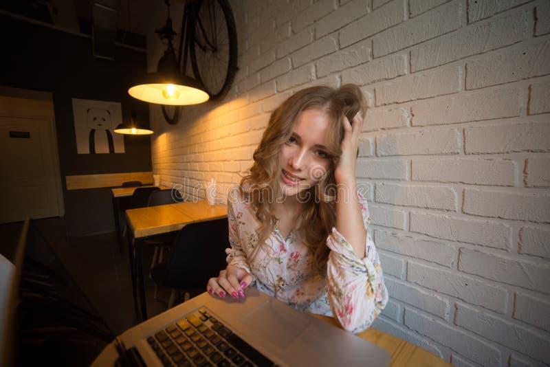 Beeld van vrij jong krullend hagelmeisje met laptop die en in een koffie glimlachen zitten stock foto's