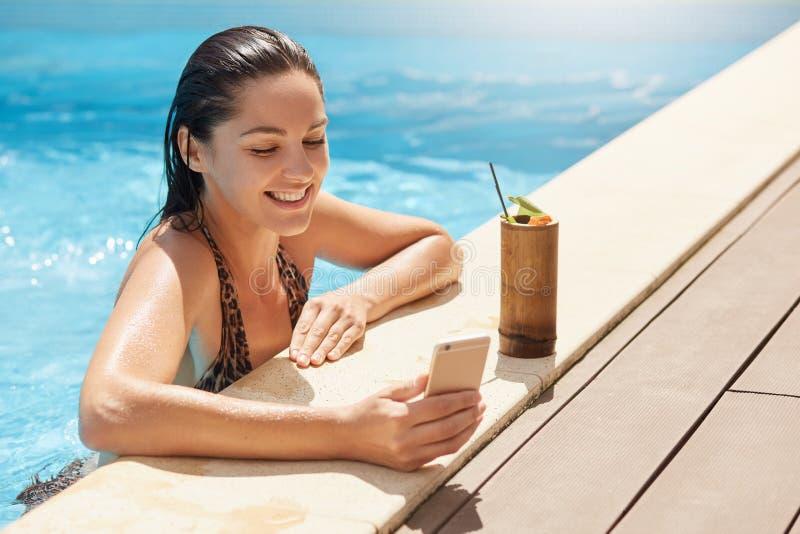 Beeld van vrolijk opgetogen model die prettige gelaatsuitdrukking hebben, die foto in zwembad nemen, die binnen zijnd oprecht gli stock foto's
