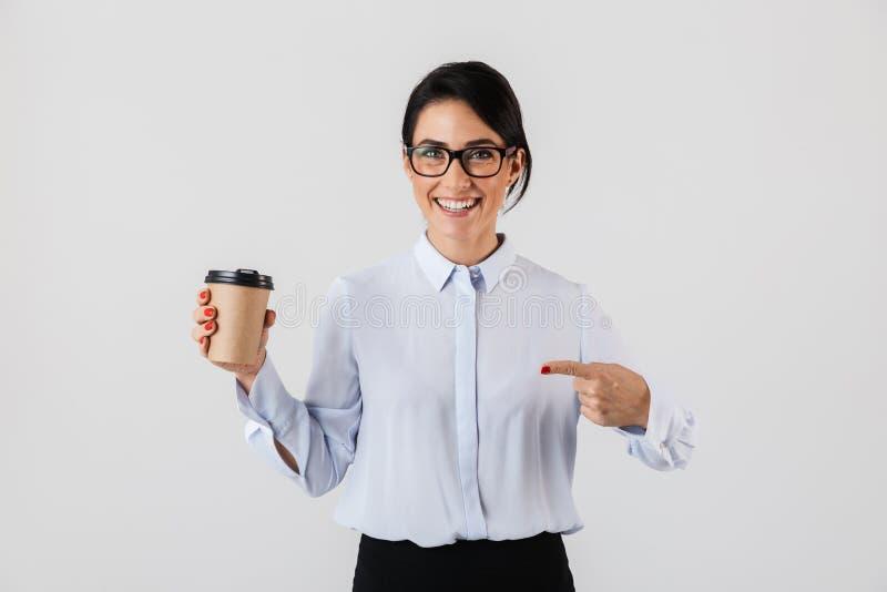 Beeld van vrolijke secretaressevrouw die oogglazen dragen die koffie van document kop in het bureau drinken, status geïsoleerd ov stock foto's