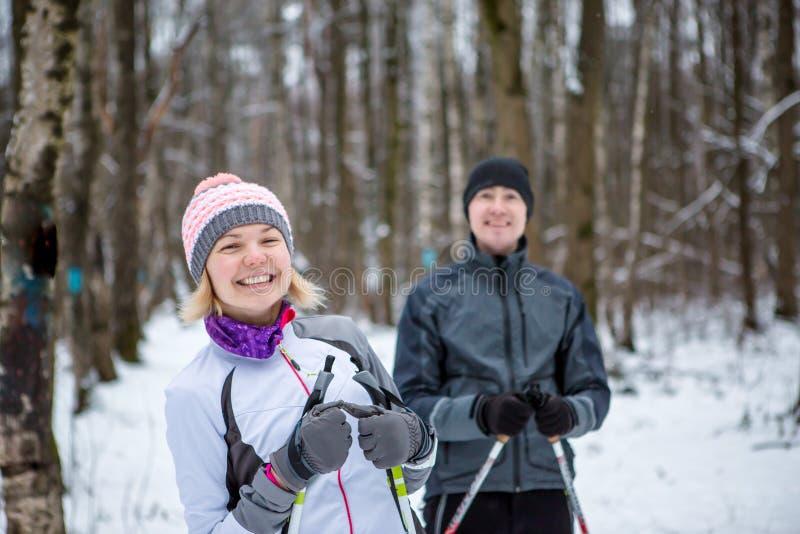 Beeld van vrolijke sportenvrouw en de mens die in de winterbos ski?en royalty-vrije stock afbeelding