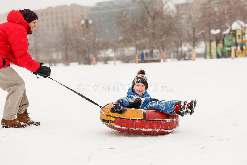 Beeld van vrolijke vader schaatsende zoon op buizenstelsel in de wintermiddag stock foto's