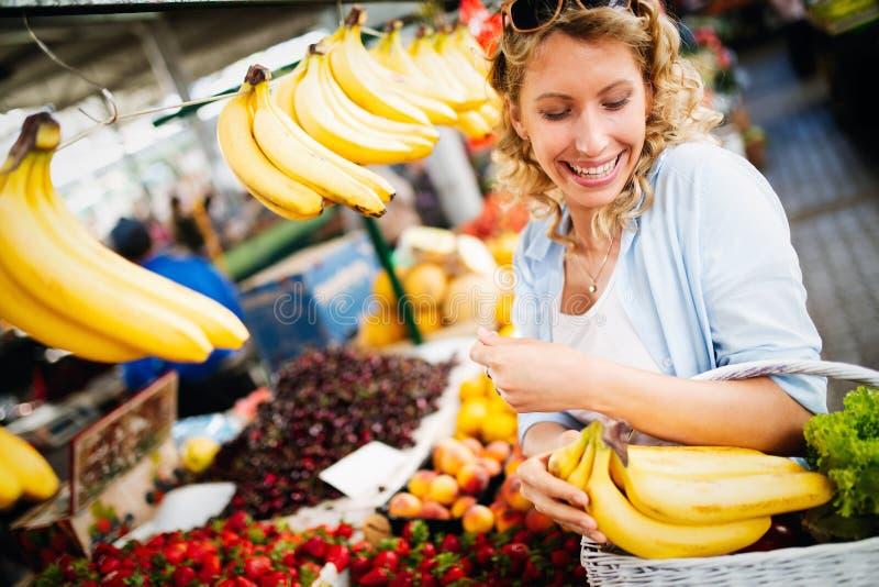 Beeld van vrouw bij markt het kopen groenten stock afbeeldingen