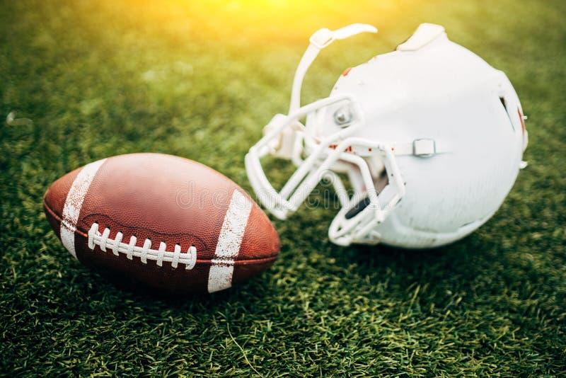 Beeld van witte helm van de voetbalster en de bal van Amerinian op groen gazon stock afbeelding