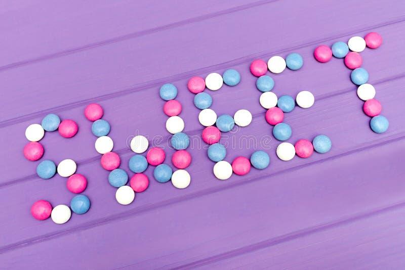 Beeld van woordsnoepje van kleurrijk suikergoed op violette achtergrond wordt gemaakt die royalty-vrije stock foto's