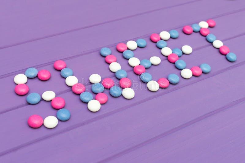 Beeld van woordsnoepje van kleurrijk suikergoed op violette achtergrond wordt gemaakt die royalty-vrije stock afbeeldingen