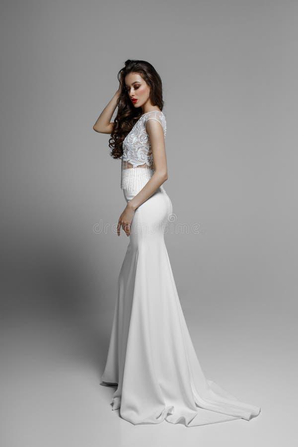 Beeld van zijaanzicht van een sexy donkerbruin model in klassieke witte huwelijkskleding, op witte achtergrond royalty-vrije stock fotografie