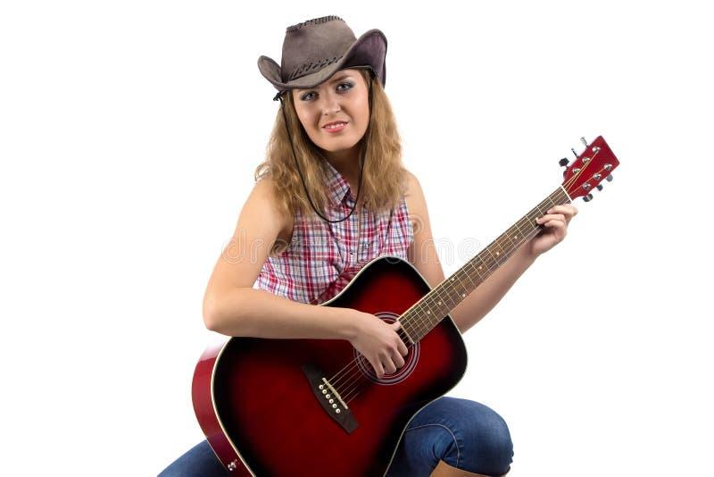 Beeld van zittingsveedrijfster met de gitaar stock foto