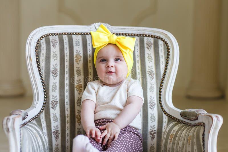 Beeld van zoet babymeisje in een kroon, close-upportret van leuk 6 maand-oud glimlachend meisje, peuter Meisje met gele boog stock foto