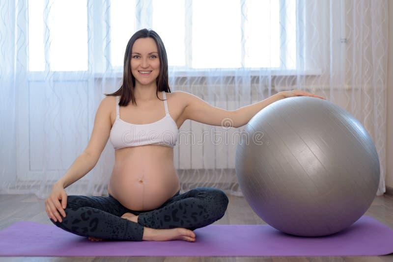 Beeld van zwangere vrouwenzitting op de vloer met fitball stock afbeelding