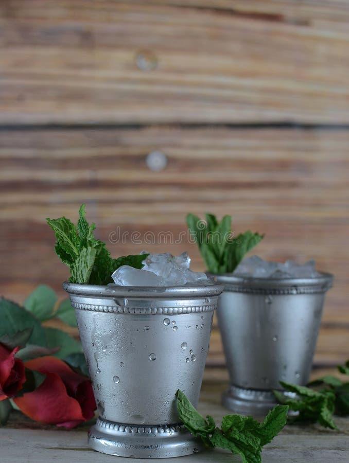 Beeld voor de Derby die van Kentucky in Mei twee zilveren koppen van het muntmedicijndrankje met verpletterd ijs en verse munt in stock afbeeldingen