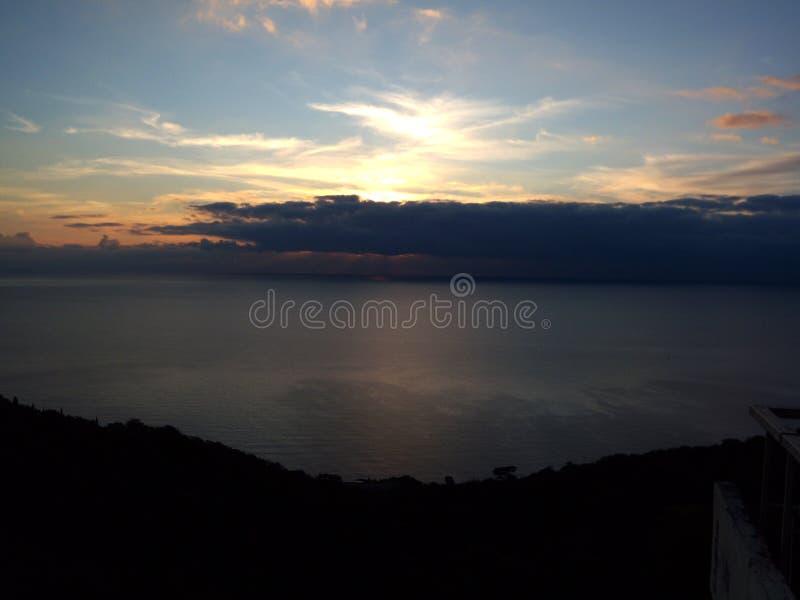 Beelden van de zonsondergang door het overzees Zonnestralen van achter grijze wolken hierboven royalty-vrije stock fotografie