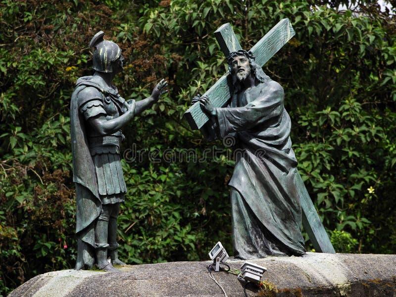Beeldhouwensemble die Jesus vertegenwoordigen die het kruis met een Roman militair dragen De manier van pelgrims aan Monserrate stock fotografie