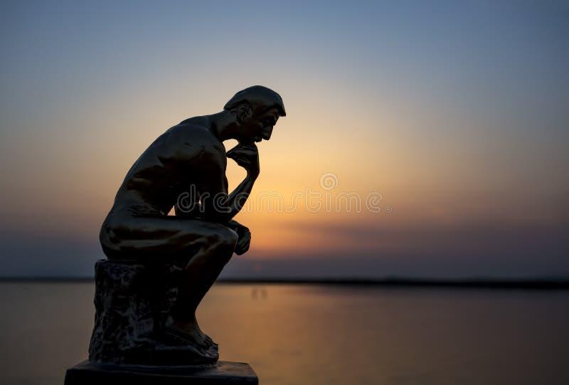 Beeldhouwwerk denkende mens in zonsondergangsilhouet De foto van het concept royalty-vrije stock afbeelding