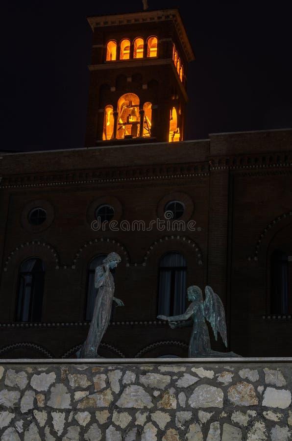 Beeldhouwwerk met een mens en engelen op hun knieën op de dijk bij nacht Nettuno, Italië stock foto