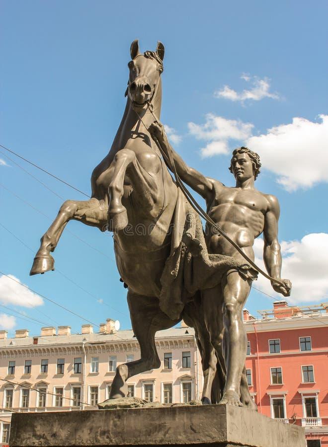 Beeldhouwwerk van de mens en paard op de Anichkov-Brug stock fotografie