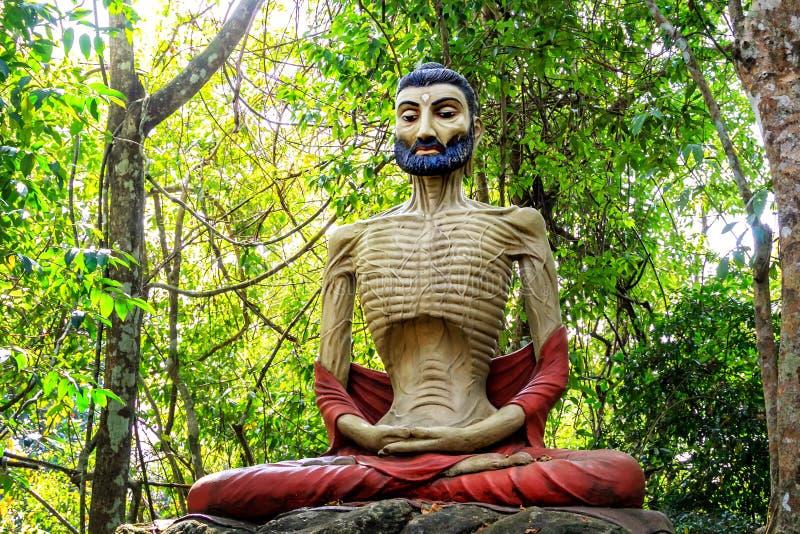 Beeldhouwwerk van een ascetische yoga in meditatie in een tropisch bos stock fotografie