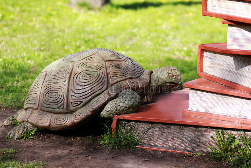 Beeldhouwwerk van een schildpad die op stapel van boeken beklimmen stock foto's