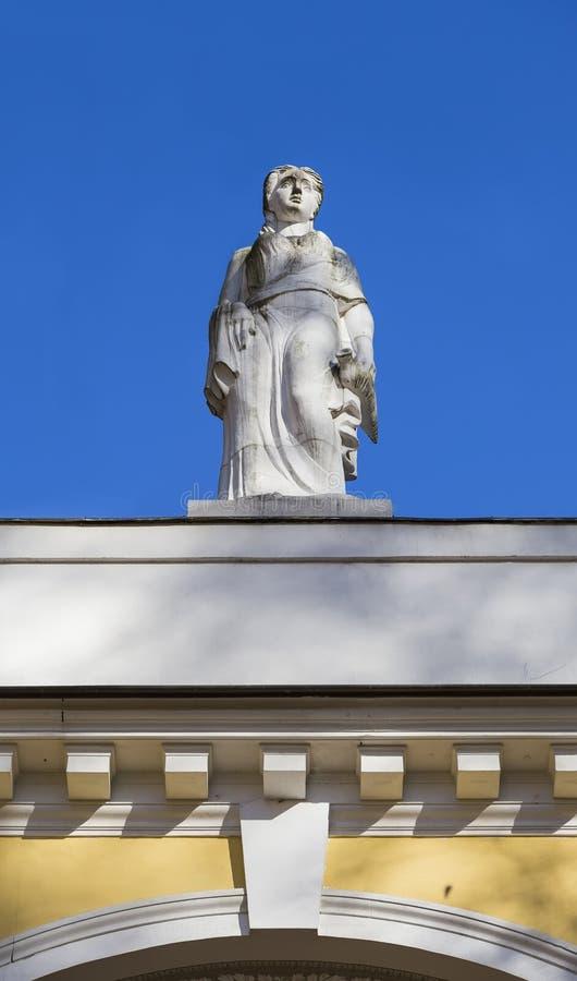 Beeldhouwwerk van een vrouw op het dak van het gebouw royalty-vrije stock afbeelding