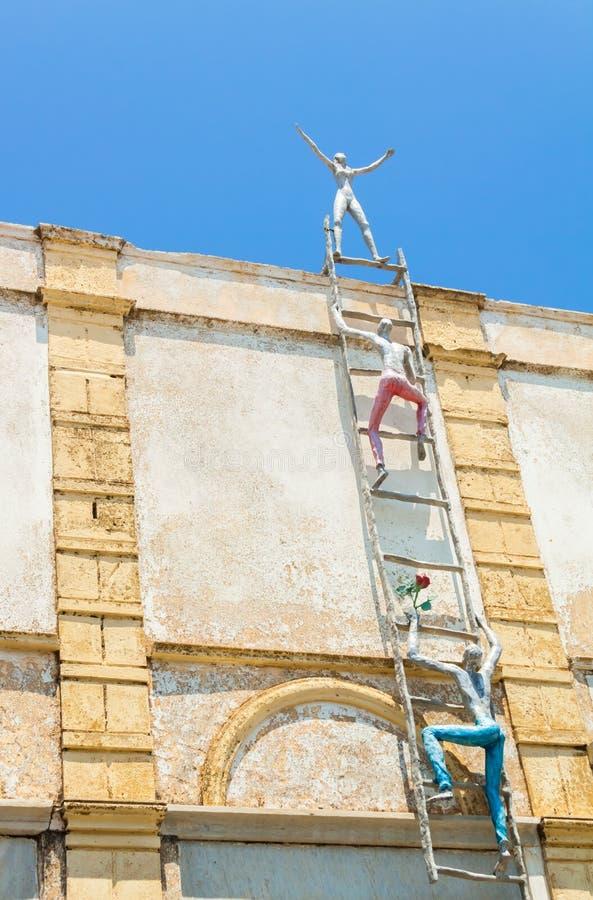 Beeldhouwwerk van mensen die een ladder op het dak in Oia dorp, Santorini beklimmen stock afbeelding