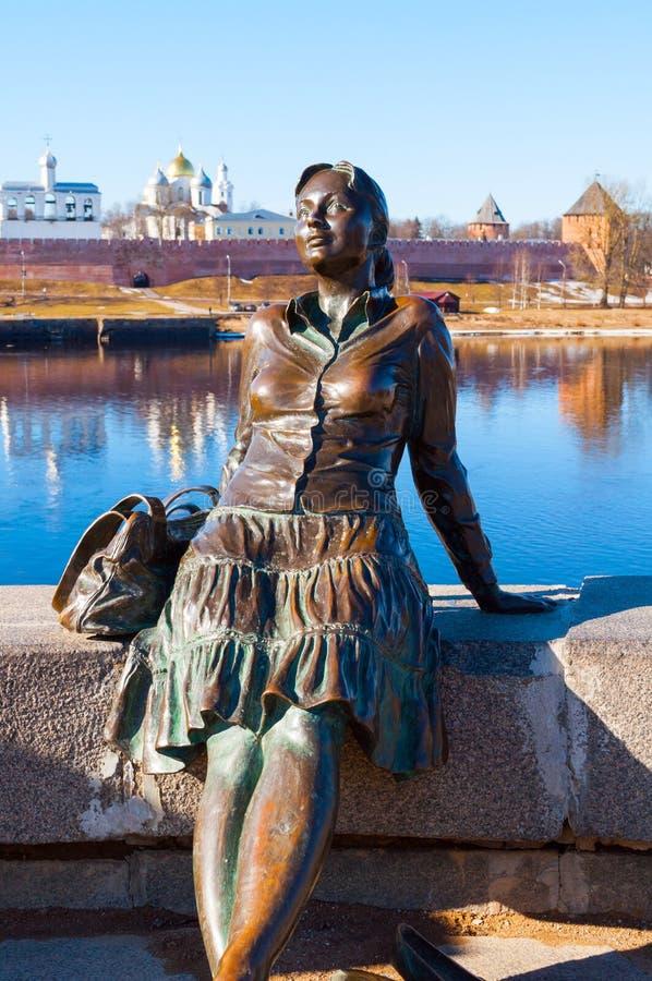 Beeldhouwwerk van vermoeid toeristenmeisje op de achtergrond van Veliky Novgorod het Kremlin in de lentedag Nadruk bij het beeldh stock afbeeldingen