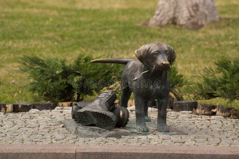Beeldhouwwerk waar een hond schoenen trekt stock fotografie