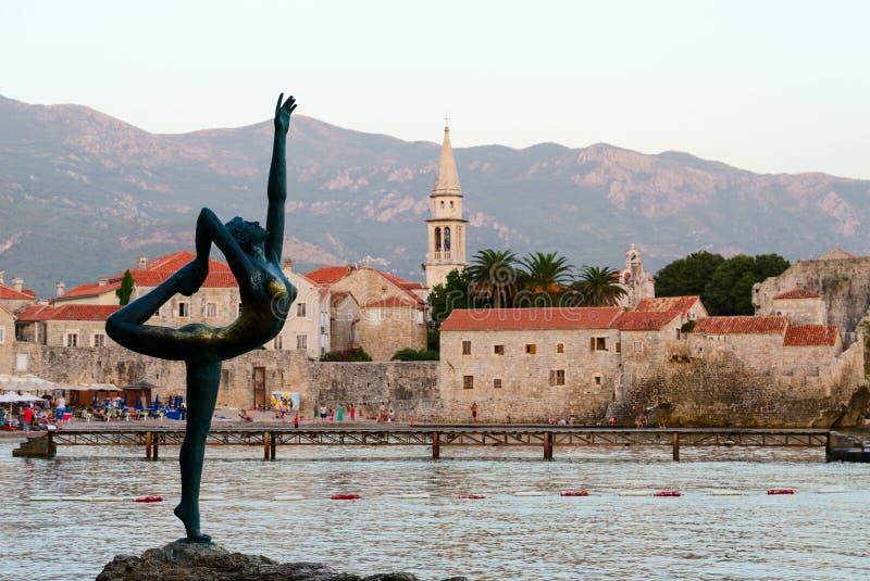 Beeldhouwwerkballerina (Danser van Budva) tegen achtergrond van oude stad royalty-vrije stock fotografie