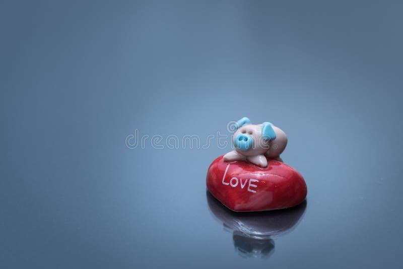 Beeldje van een leuk klein varken die op een rode steen liggen stock afbeelding