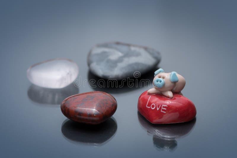 Beeldje van een leuk klein varken die op een rode steen liggen stock foto's
