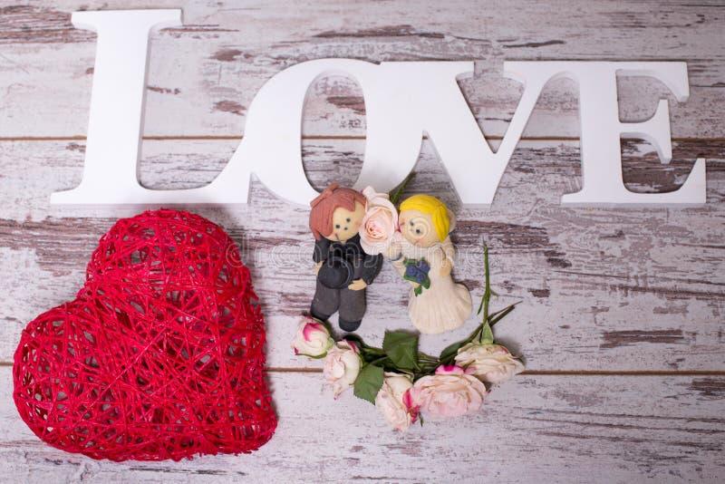 Beeldjes van de bruid en de bruidegom die de verplichting aan liefde symboliseert royalty-vrije stock afbeeldingen
