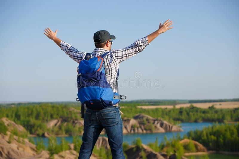 Beeldrug van de toeristenmens met rugzak, handen omhoog op heuvel op achtergrond van berguitgestrektheden, blauwe hemel royalty-vrije stock afbeeldingen
