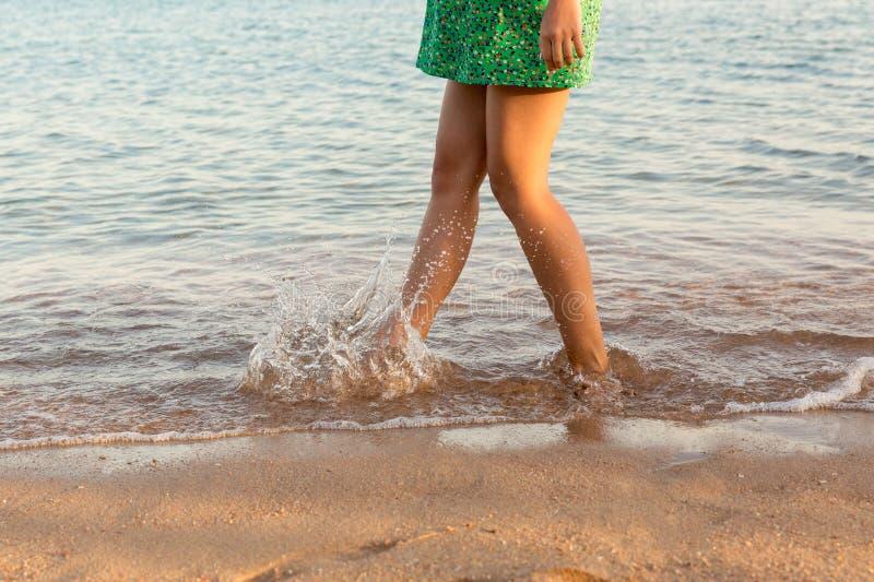 Been die van vrouw op strand met water het bespatten lopen De vakantie van de zomer benen van een meisje die in water op zonsonde royalty-vrije stock foto