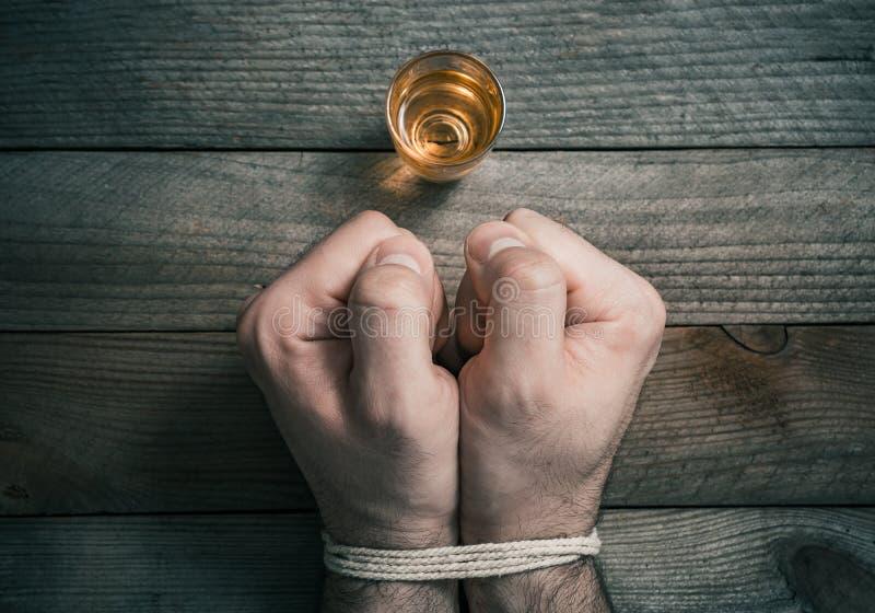 Beendigtes trinkendes Alkohol-Konzept mit einem Schnaps-Glas in Front Of 2 gebundene betonte schauende geballte Fäuste lizenzfreie stockfotos