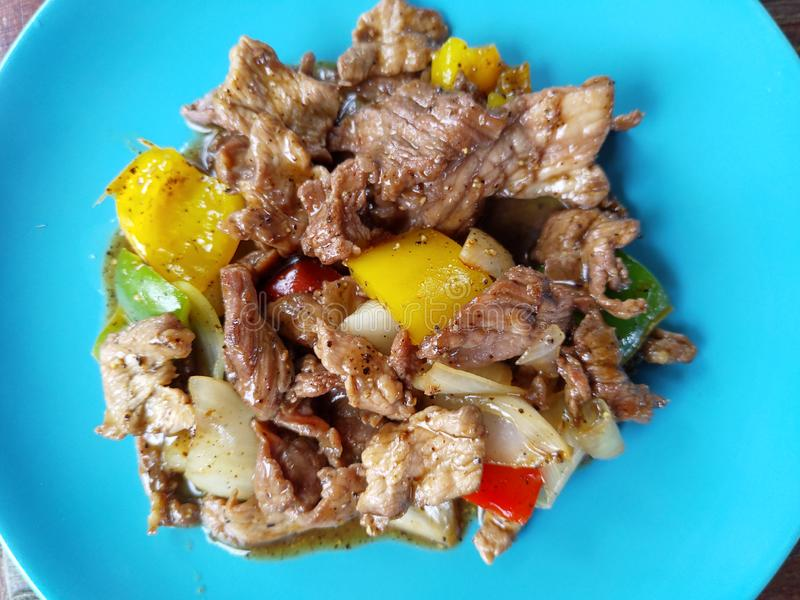 Beef stir fried black pepper on blue plate. Beef stir fried black pepper with paprika, onions, coriander on blue plate stock photo