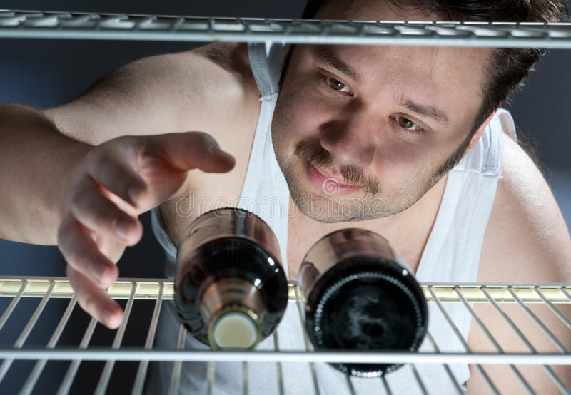 Beer. Fat man gets beer from the fridge royalty free stock photo