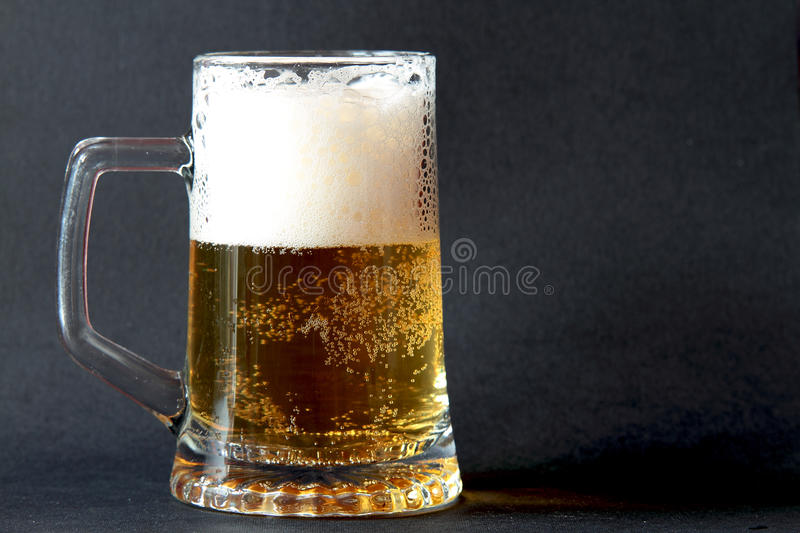 Glass of frothy beer royalty free stock photos