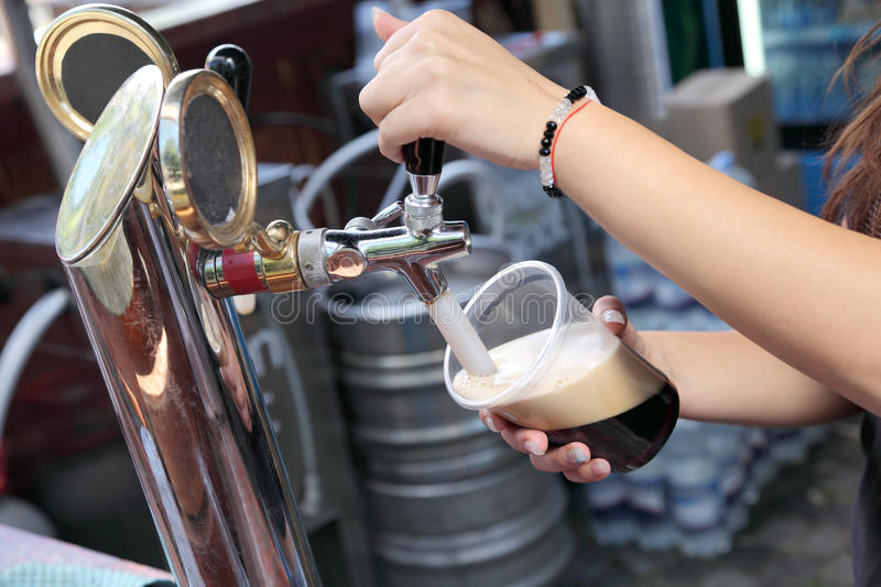 Beer. Pouring dark beer to plastic glass from beer tap royalty free stock images