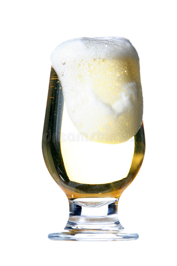 Beer. A full glass of beer pouring foam out royalty free stock photography