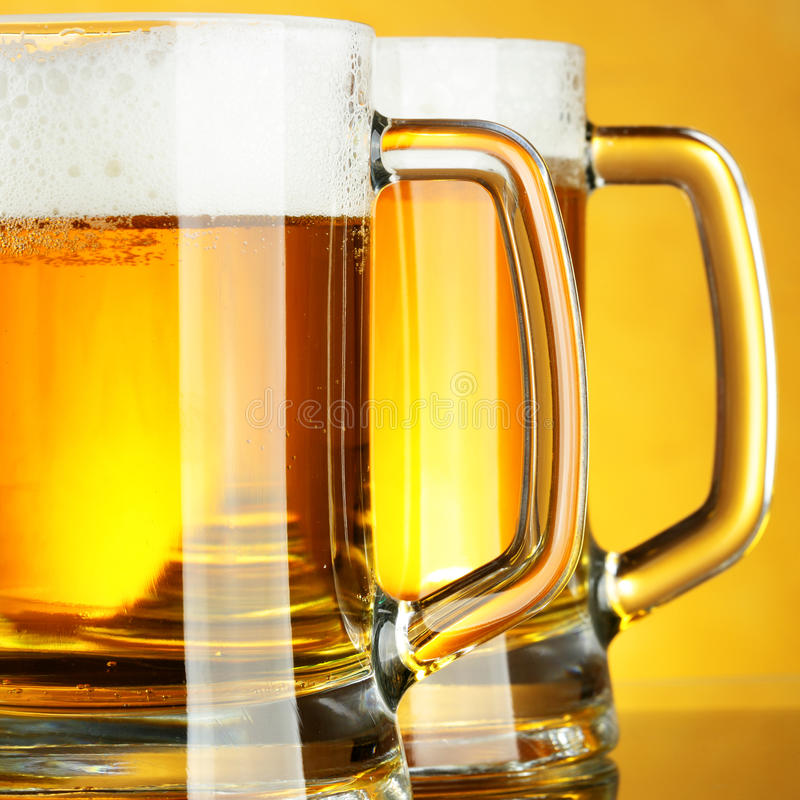 Beer. Mugs with froth over yellow background royalty free stock images