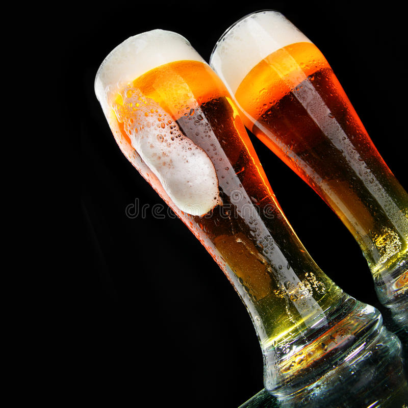 Beer. Glasses of beer with froth over black background royalty free stock photo