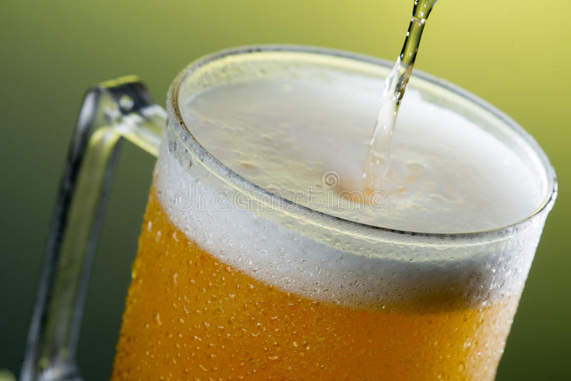 Beer. Glass with beer in a yellow background royalty free stock images