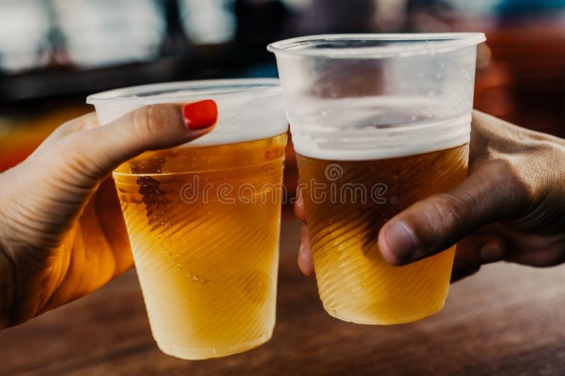 Hand of man and woman holding glasses with beer. Beer appointment. A hand with a woman with a manicure holds a plastic glass with beer. The second glass in the stock photos