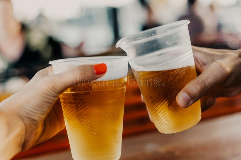 Hand of man and woman holding glasses with beer. Beer appointment. A hand with a woman with a manicure holds a plastic glass with beer. The second glass in the royalty free stock photo