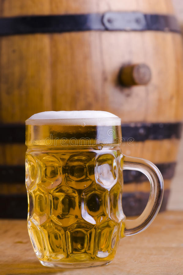 Beer barrel. Full glass of beer with wooden barrel, blond beer with foam royalty free stock photography