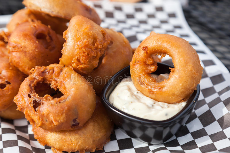Beer Batter Onion Rings. A order of beer battered onion rings with white tartar dipping sauce at a patio table stock images