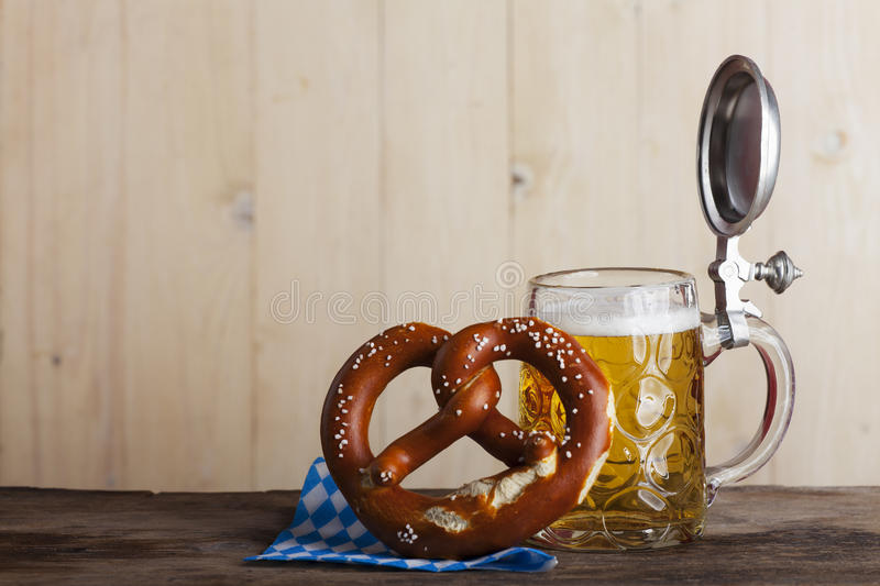 Beer. Bavarian beer and a pretzel on wood royalty free stock photo