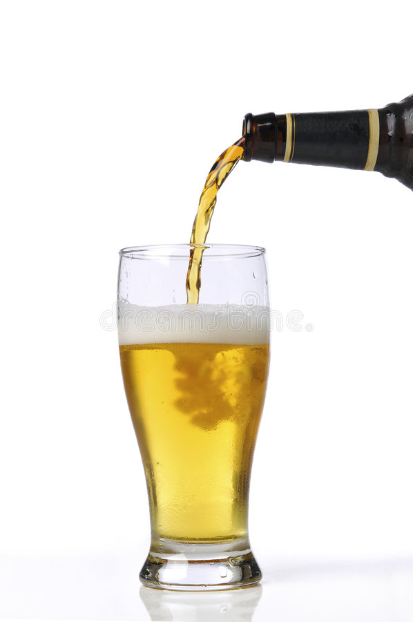 Beer being pour on a glass. Isolated against a white background stock images