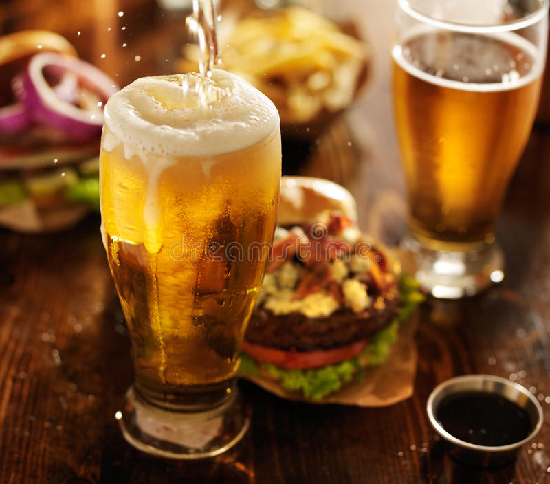 Beer being poured into glass. With gourmet hamburgers in background royalty free stock photo
