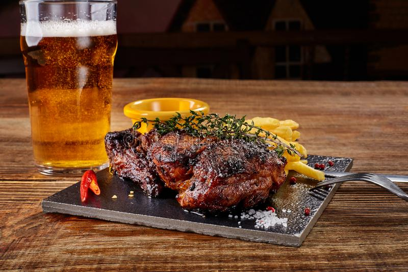 Beer being poured into glass with gourmet steak and french fries on wooden background. stock photos